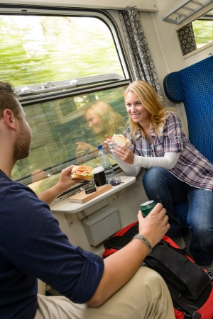 Couple traveling by train eating sandwiches hungry smiling woman man photo