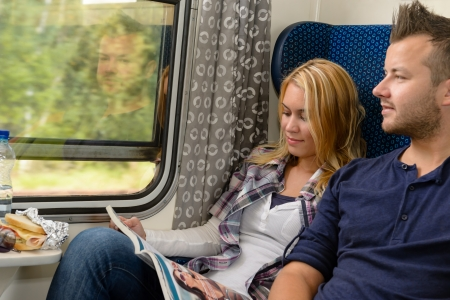 Woman reading magazine man looking train window happy travel vacation photo