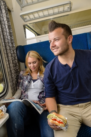 Man looking out train window woman magazine sandwich reading smiling photo