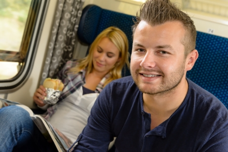 Man smiling sitting on train woman sandwich vacation traveling journey Stock Photo - 16968320