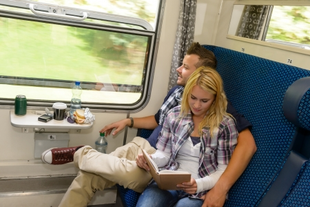 Man looking out train window woman reading couple happy traveling Stock Photo - 16968367