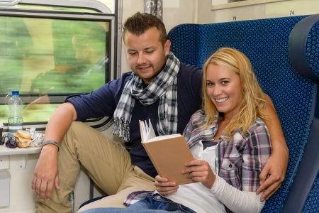Couple traveling by train woman reading smiling vacation man sitting Stock Photo - 16968397