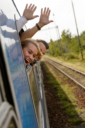 Couple waving with heads out train window enthusiastic woman man photo