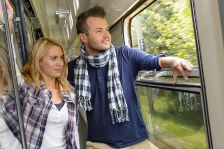 Couple looking out the train window smiling woman man vacation photo