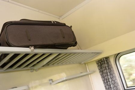 unattended: Baggage sitting on train rack in compartment travel vacation nobody