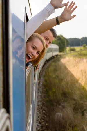 Couple screaming out train window waving happy excited laughing vacation photo