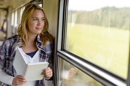 mujer pensativa: Libro de lectura de la mujer mirando por la ventana del tren vacaciones viajar sonriente Foto de archivo