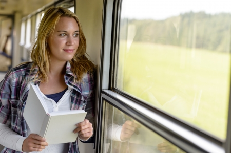 look pleased: Woman reading book looking out train window smiling vacation traveling