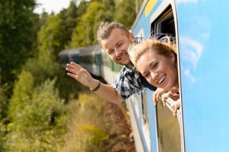 Couple agitant avec la tête hors fenêtre du train enthousiaste heureux sans soucis