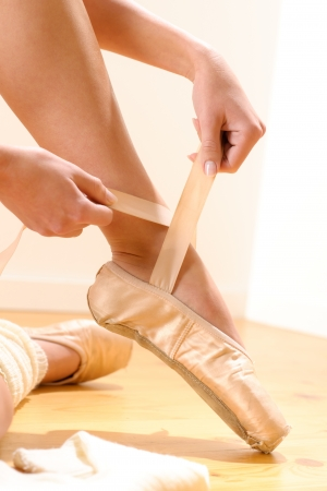 ballet slippers: Ballet dancer tying slippers around her ankle woman ballerina pointe Stock Photo