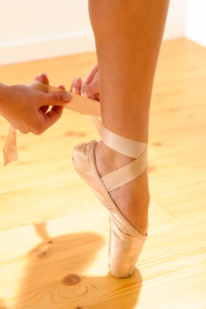 pointe shoe: Close-up of a female ballet dancer tying her pointe shoe