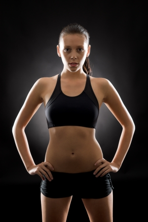 Portrait of sporty young woman standing akimbo on black background Stock Photo - 16969645
