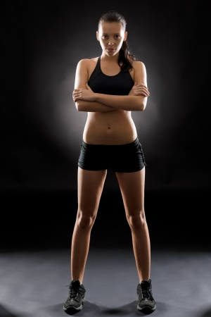Sporty young woman standing with arms crossed on black background photo