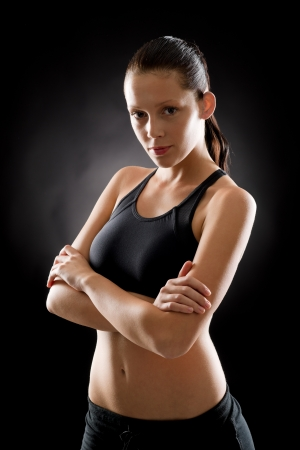 woman black background: Sporty young woman standing with arms crossed on black background Stock Photo