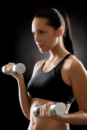Sporty young woman holding dumbbells on black background Stock Photo - 16969617