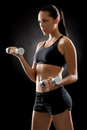 Sporty young woman holding dumbbells on black background Stock Photo - 16969639