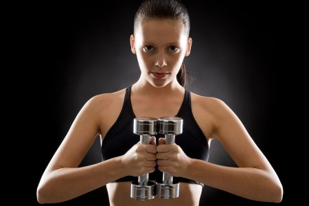 Portrait of sporty young woman holding dumbbells on black background Stock Photo - 16969641
