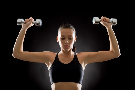 Portrait of sporty young woman holding dumbbells on black background Stock Photo - 16985367