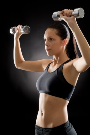 Portrait of sporty young woman holding dumbbells on black background Stock Photo - 16985384