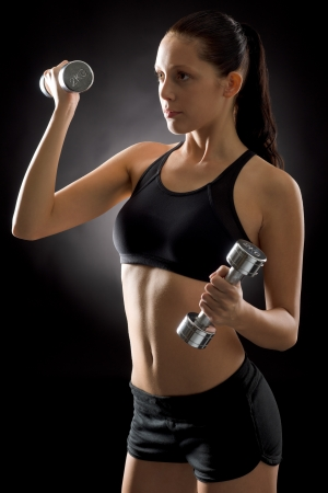 Sporty young woman holding dumbbells on black background Stock Photo - 16985385