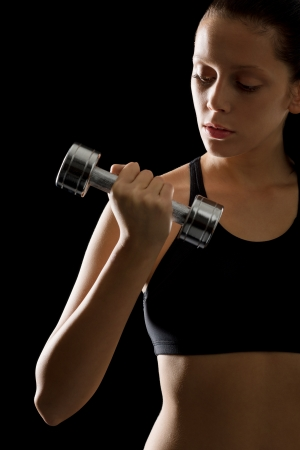 Portrait of sporty young woman holding dumbbell on black background Stock Photo - 16985368