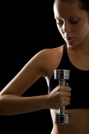 Young woman holding fitness dumbbell on black background Stock Photo - 16985369