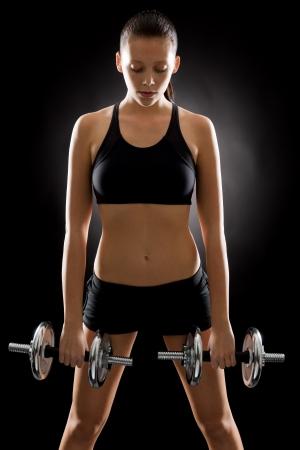 adjustable dumbbell: Fitness young woman holding adjustable dumbbells on black background
