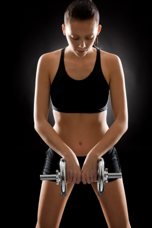 adjustable dumbbell: Sporty young woman holding adjustable dumbbell on black background Stock Photo