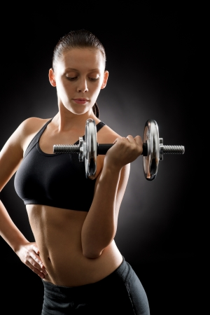 Young sport woman holding adjustable dumbbell on black background Stock Photo - 16985382