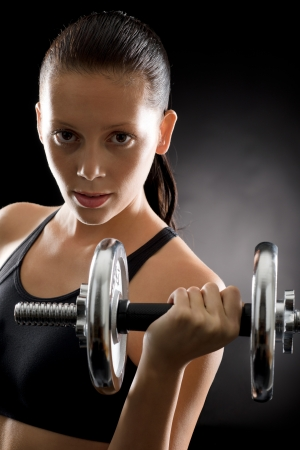Sporty young woman holding adjustable dumbbell on black background Stock Photo - 16985403