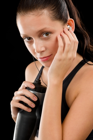 Young fitness woman with headphones and bottle on black background Stock Photo - 16969622