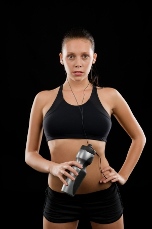 Sporty young woman posing with headphones and bottle black background Stock Photo - 16969637