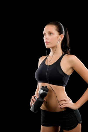 Sporty young woman with headphones and bottle on black background Stock Photo - 16969633