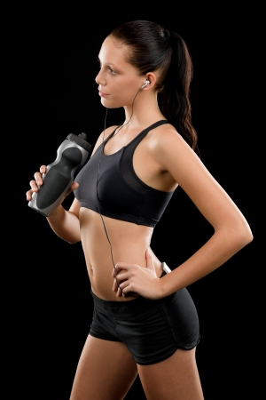 Sporty young woman with headphones and bottle on black background Stock Photo - 16969634