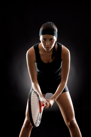 Young female tennis player ready to play on black background photo