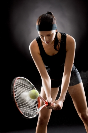 Young female tennis player ready to hit ball black background photo