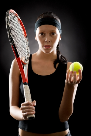 Female tennis player with racket and balll on black background photo