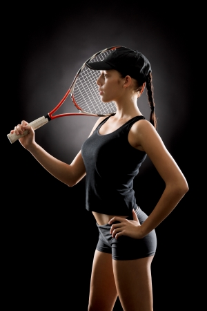 Jeune joueur de tennis féminin posant avec la raquette sur fond noir Banque d'images