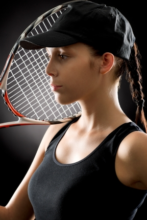 Tennis woman portrait female player with racket on black background photo