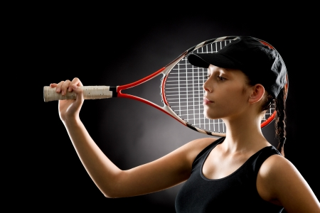 Young female tennis player posing with racket on black background Stock Photo - 16969636