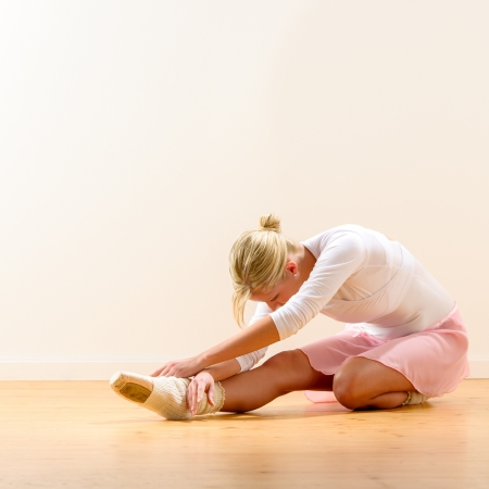 Beautiful ballerina warming up on the floor bending on knee Stock Photo - 16984866