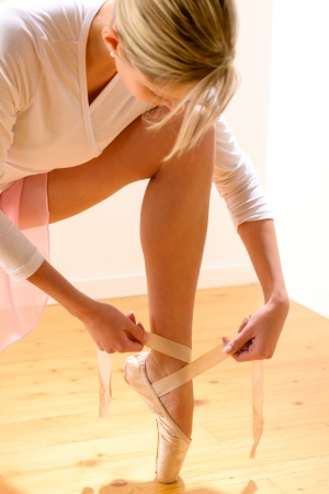 Ballet dancer getting ready for ballet performance woman ballerina tying photo