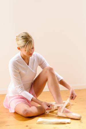 Ballerina getting dressed for ballet performance woman pointe tying dressing Stock Photo - 16984872