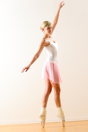 ballet slippers: Beautiful ballerina on tiptoe with raised arm dancing pointe Stock Photo