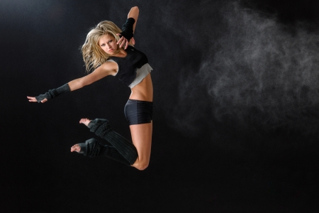 Contemporary dancer woman jumping dance on black background photo