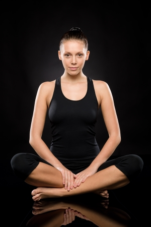 yoga pants: Young Caucasian woman doing yoga legs crossed meditating relaxing pose Stock Photo