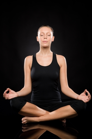 Young woman sitting in lotus position meditating with eyes closed Stock Photo - 17160265