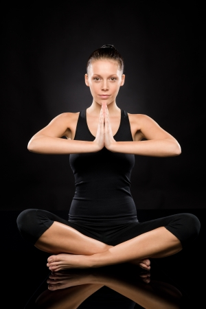 Woman performing yoga sitting on the floor with clasped hands Stock Photo - 17160270
