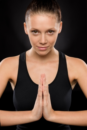 Portrait of smiling young woman performing yoga with hands clasped Stock Photo - 17160242