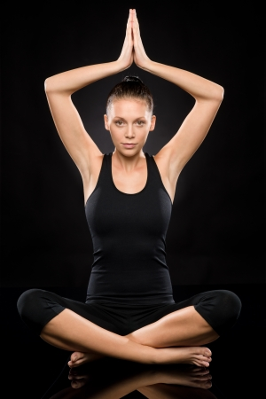 above head: Young woman performing yoga with raised clasped hands lotus position Stock Photo